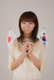 Mujer joven que sostiene el indicador japonés y el indicador coreano Fotos de archivo
