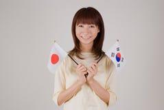 Mujer joven que sostiene el indicador japonés y el indicador coreano Fotografía de archivo