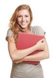 Mujer joven que sostiene el libro rojo Imagen de archivo
