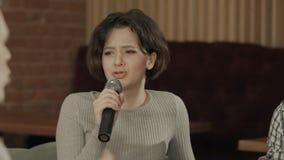 Mujer joven que sostiene el micrófono y que canta en el Karaoke Fotografía de archivo libre de regalías