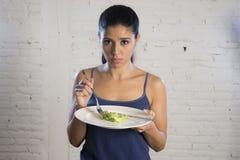 Mujer joven que sostiene el plato con lechuga ridícula como su símbolo de la comida del trastorno alimenticio loco de la dieta Imágenes de archivo libres de regalías