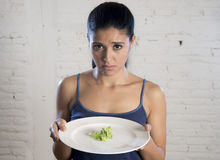 Mujer joven que sostiene el plato con lechuga ridícula como su símbolo de la comida del trastorno alimenticio loco de la dieta Imagen de archivo