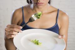 Mujer joven que sostiene el plato con lechuga ridícula como su símbolo de la comida del trastorno alimenticio loco de la dieta Fotografía de archivo
