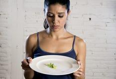 Mujer joven que sostiene el plato con lechuga ridícula como su símbolo de la comida del trastorno alimenticio loco de la dieta Foto de archivo libre de regalías