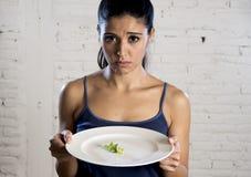 Mujer joven que sostiene el plato con lechuga ridícula como su símbolo de la comida del trastorno alimenticio loco de la dieta Imagen de archivo libre de regalías