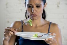 Mujer joven que sostiene el plato con lechuga ridícula como su símbolo de la comida del trastorno alimenticio loco de la dieta Fotos de archivo