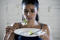 Mujer joven que sostiene el plato con lechuga ridícula como su símbolo de la comida del trastorno alimenticio loco de la dieta Fotografía de archivo libre de regalías