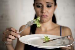 Mujer joven que sostiene el plato con lechuga ridícula como su símbolo de la comida del trastorno alimenticio loco de la dieta Imagenes de archivo