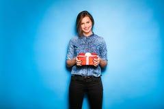 Mujer joven que sostiene el regalo rojo en manos Foto de archivo libre de regalías