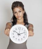 Mujer joven que sostiene el reloj Imagen de archivo libre de regalías