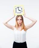 Mujer joven que sostiene el reloj grande Fotografía de archivo libre de regalías