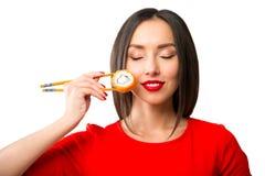 Mujer joven que sostiene el sushi con palillos, aislados en blanco Foto de archivo libre de regalías
