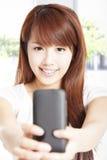 Mujer joven que sostiene el teléfono elegante Imagen de archivo libre de regalías