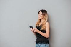 Mujer joven que sostiene el teléfono móvil y que mira para arriba el copyspace Fotos de archivo libres de regalías