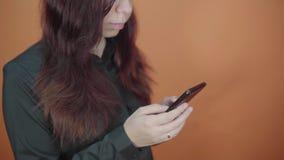 Mujer joven que sostiene el tel?fono m?vil a disposici?n en fondo anaranjado Femenino mecanografiando un mensaje en un smartphone almacen de video