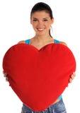 Mujer joven que sostiene la almohadilla en forma de corazón Imagen de archivo