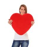 Mujer joven que sostiene la almohadilla en forma de corazón Foto de archivo libre de regalías