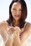 Mujer joven que sostiene la arena en manos al aire libre Fotos de archivo