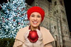 Mujer joven que sostiene la bola de la Navidad cerca de Duomo en Florencia, Italia Imagen de archivo libre de regalías