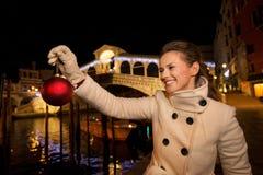Mujer joven que sostiene la bola de la Navidad cerca del puente de Rialto en Venecia Fotos de archivo libres de regalías