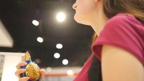 Mujer joven que sostiene la botella de perfume y que rocía fragancia en la tienda La muchacha asperja perfume en cuello Concepto  metrajes