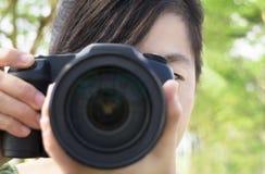 Mujer joven que sostiene la cámara de la foto imagen de archivo