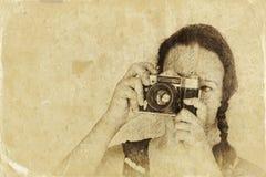 Mujer joven que sostiene la cámara vieja imagen filtrada, foto del viejo estilo imágenes de archivo libres de regalías