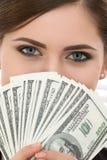 Mujer joven que sostiene la fan de cientos retratos de los billetes de dólar fotos de archivo libres de regalías