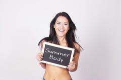 Mujer joven que sostiene la pizarra que dice el cuerpo del verano Imagen de archivo