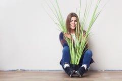 Mujer joven que sostiene la planta verde grande que se sienta contra la pared Foto de archivo libre de regalías