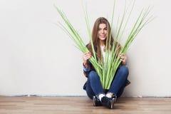 Mujer joven que sostiene la planta verde grande que se sienta contra la pared Imágenes de archivo libres de regalías