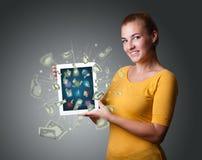 Mujer joven que sostiene la tableta con el dinero Foto de archivo libre de regalías