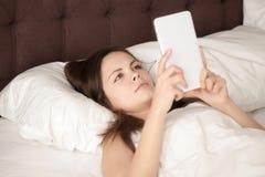 Mujer joven que sostiene la tableta digital que miente en la cama, leyendo el eBook Foto de archivo libre de regalías