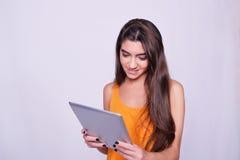 Mujer joven que sostiene la tableta en fondo gris Imagen de archivo