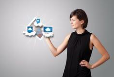 Mujer joven que sostiene la tablilla con los dispositivos modernos en nubes Imagen de archivo libre de regalías