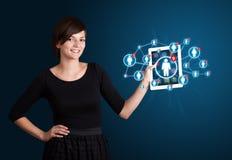 Mujer joven que sostiene la tablilla con los iconos sociales de la red Imagen de archivo libre de regalías