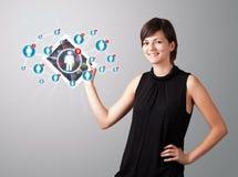Mujer joven que sostiene la tablilla con los iconos sociales de la red Imágenes de archivo libres de regalías