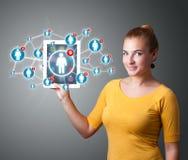 Mujer joven que sostiene la tablilla con los iconos sociales de la red Fotografía de archivo