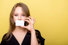Mujer joven que sostiene la tarjeta de banco aislada en un fondo amarillo Fotos de archivo libres de regalías