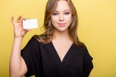 Mujer joven que sostiene la tarjeta de banco aislada en un fondo amarillo Fotografía de archivo