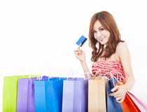Mujer joven que sostiene la tarjeta de crédito con los bolsos de compras Imagenes de archivo
