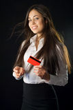 Mujer joven que sostiene la tarjeta de crédito roja imagen de archivo