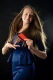 Mujer joven que sostiene la tarjeta de crédito roja fotografía de archivo libre de regalías