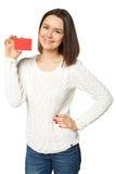 Mujer joven que sostiene la tarjeta de crédito vacía, sobre el fondo blanco Foto de archivo libre de regalías