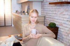 Mujer joven que sostiene la taza de té en casa imagen de archivo libre de regalías