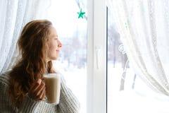 Mujer joven que sostiene la taza de té en manos, mirando a través de la ventana Foto de archivo libre de regalías