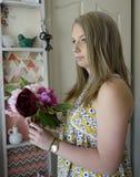 Mujer joven que sostiene las flores. Imagen de archivo libre de regalías