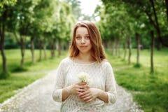 Mujer joven que sostiene las flores al aire libre Fotografía de archivo libre de regalías