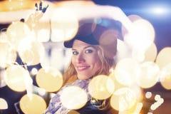 Mujer joven que sostiene las guirnaldas en al aire libre en ciudad imagen de archivo libre de regalías