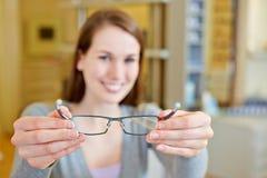 Mujer joven que sostiene los nuevos vidrios Imagen de archivo libre de regalías